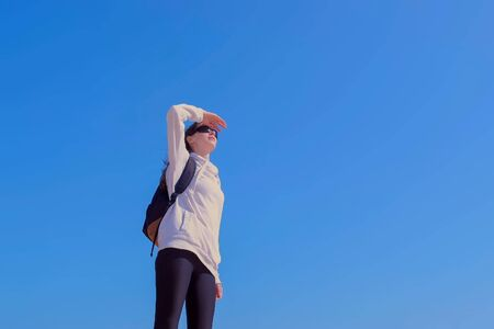 Woman traveller in sunglasses is looking into the distance on the sides putting a hand to her forehead. She stands on blue sky background in sunny day. Wearing in sportwear with backpack.