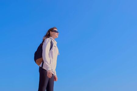 Young woman traveller with backpack in sunglasses is enjoying nature on blue sky background. She is standing and looking at sky. Escape of reality. Freedom and carefree life.