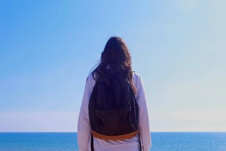 Girl brunette traveller with backpack is looking at sea standing on center, back view. She is in white hoodie. Sea and clear sky at sunny day on background. Imagens