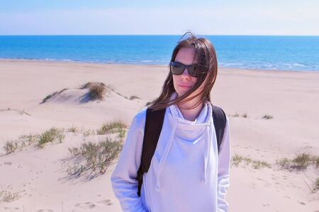 Woman on empty eashore off-season. Portrait of young woman traveller with backpack on sea sand beach on vacation. Brunette in sunglasses is enjoying nature. Imagens
