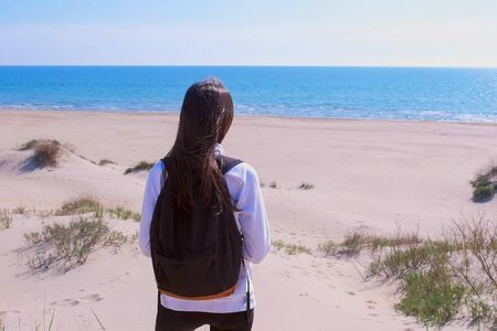 Girl traveller with backpack on sea vacation. She is standing on the sea sand beach and looking at sea, back view. Tourist is resting on sea off-season, empty beach.