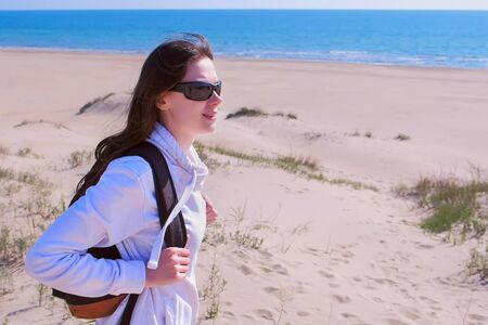 Young girl on sea walking on empty beach off-season. Woman traveller with backpack is looking around in sea sand beach on vacation. Brunette in sunglasses, hoodie and leggings. Imagens