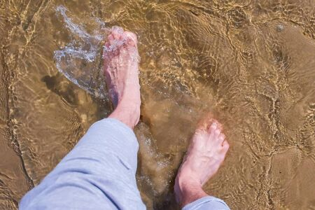 Mans barefooted feet on trousers. Man is walking on water shallow on sand bottom, legs close up. Enjoying summer vacation. 版權商用圖片