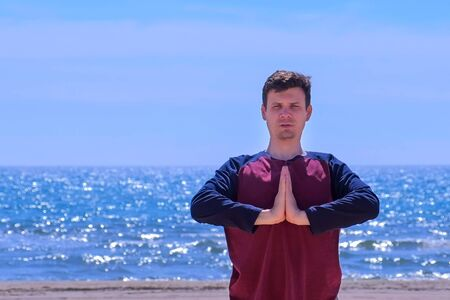 Yoga training on the beach. Portrait of young man is meditating on the sea beach putting hands in namaste pose. Outdoor sport activity.