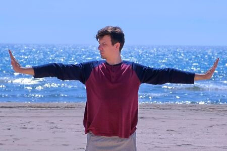 Young man on yoga training on the seaside. Man is warming up on the beach before yoga practice. Newcomer in sport yoga exercises. Outdoor sport activity.