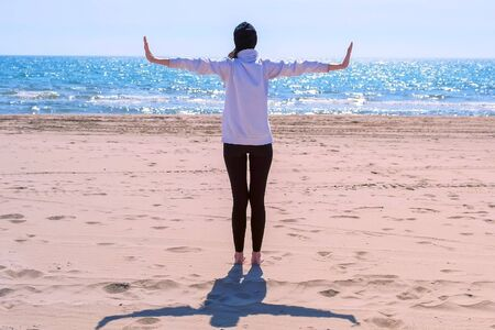 Woman in hoodie, leggings and hat is standing on sand sea beach with arms out to sides making yoga exercise. Healthy and sport concept. Outdoor sport activity.
