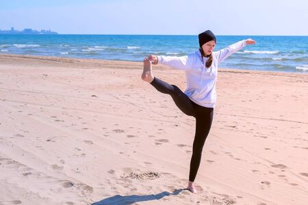 Woman practices yoga on sea beach on sand. She makes exercise raises her leg and holds it hand in balance pose. She is standing on one leg, beginner in yoga training.