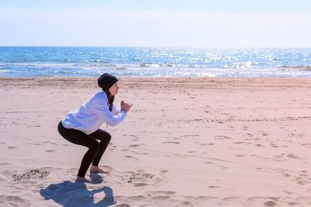 Young woman in hoodie, hat and leggings on sea sand beach. She does squats execises training her booty, side view. Fitness outdoor sport concept.