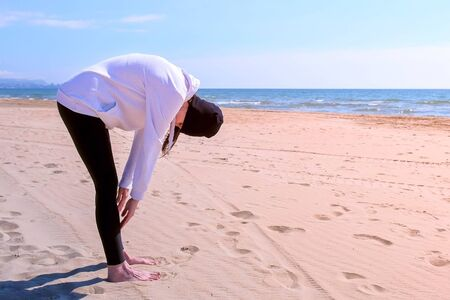 Young girl in hoodie, hat and leggings on sea sand beach. She makes squats execises training her booty, side view. Fitness outdoor sport concept.