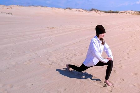 Young girl does High Lunch Pose on sea sand beach. She is beginner in yoga practice. Training and sport exercises outdoor. She is wearing hoodie, leggings and hat.
