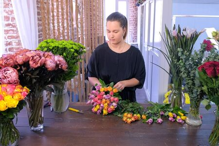 Floral business concept. Professional florist woman makes bouquet from small colourful roses works in flower shop. She puts flowers in bunch creates composition in floristic studio salon store.