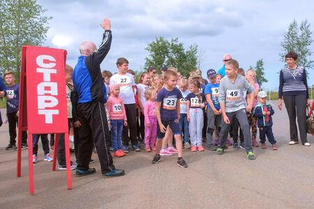 Kirov, Russia, 17-08-2019: Children running competitions in city, start jogging. Kids with numbers on backs are on starting line waiting to go. Trainer gives the signal to start. Editorial video. Editöryel