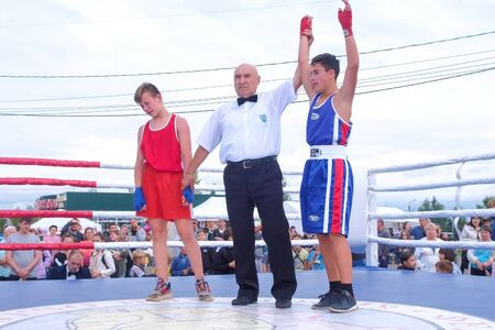 Kirov, Russia, 17-08-2019: Judge raises up hand of winning teenager boxer. Crowd of spectators in city Park. Concept of childrens sports and healthy lifestyle. Editorial video.