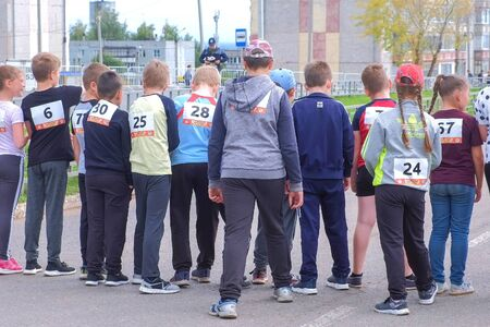 Kirov, Russia, 17-08-2019: Childrens running competitions in the city. Kids with numbers on their backs are on the starting line. Childrens sports and healthy lifestyle. Editorial video. Editöryel