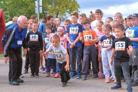 Kirov, Russia, 17-08-2019: Children running competitions in city, start jogging. Kids with numbers on backs are on starting line waiting to go. Children sports and healthy lifestyle. Editorial video.