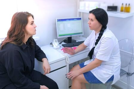 Woman in consultation with a trichologist in clinic talking about her problems with hairs. Woman doctor asks questions and listens carefully to patient. Hairs cure and therapy.