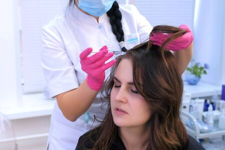 Doctor trichologist making injections mesotherapy in young woman skin head for hair growth in cosmetology clinic, closeup view. Cosmetologist making treatment procedure to patient. Reklamní fotografie