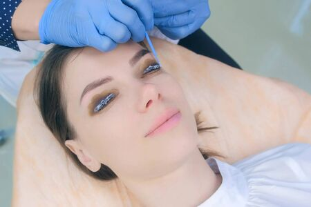 Beautician applying solution for lamination on woman lashes on curlers, lift eyelashes procedure in beauty salon, face closeup. Cosmetologist making lash lifting in cosmetology clinic, hands closeup.