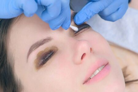 Beautician wiping cotton stick solution from lashes, lamination lift eyelashes procedure in beauty salon, face closeup. Cosmetologist making lash lifting in cosmetology clinic, hands closeup. Imagens