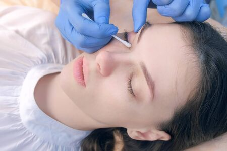 Beautician wipes around eyes cotton sticks after lashes lamination lifting procedure in beauty salon, face closeup. Cosmetologist making lash lifting in cosmetology clinic, hands closeup.