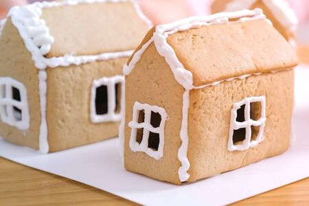 Make windows from sugar sweet icing on gingerbread house. Cooking homemade gingerbread house Reklamní fotografie