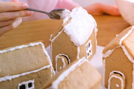 Womans hands put the roof of gingerbread house with sugar sweet icing on. Cooking homemade gingerbread house