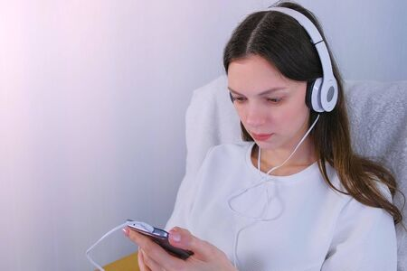 Woman watches serial on mobile phone in headphones