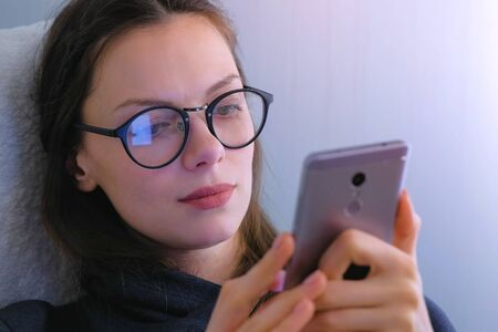 Woman in glasses watches serial on mobile phone. Face close-up