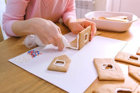 Womans hands make gingerbread house glues details with sugar sweet icing. Cooking homemade gingerbread house Reklamní fotografie