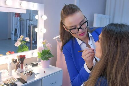 Makeup artist applies lipstick uses brush on model girl lips in beauty salon. Professional visagiste styist working making make up in cosmetology. Glamour fashion industry. Beauty business concept.