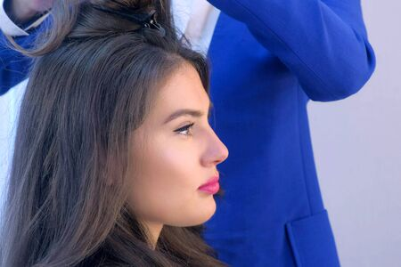 Face of young woman in beauty salon on hairstyle with hairdresser, side view. Glamour fashion industry. Beauty business concept. Hairdresser making hairdo combing hairs for beautiful girl. Reklamní fotografie