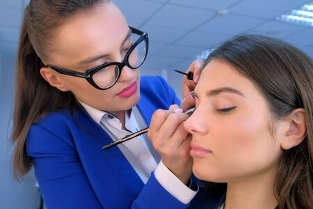 Make up artist making arrows on girl eyelids with brush in beauty salon. Glamour stylish fashion industry. Beauty business concept. Young woman model. Visagiste stylist working.