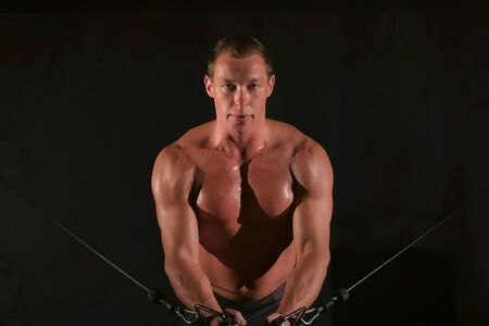 Man bodybuilder training chest muscles exercise using cable crossover machine and looking at camera, front view. White smoke in gym in dark. Sport motivation. Fit model with perfect body, naked torso.