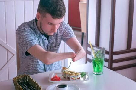 Problem of adaptation to usual life guy without wrists. Disabled man with two amputated stump hands eats sushi rolls in cafe with fork. Independent Invalid person with disabilities. Reklamní fotografie