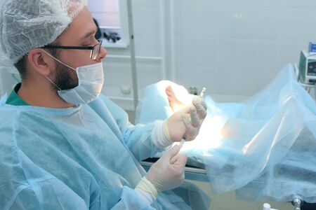 Surgeon man is typing in syringe drug for local anesthesia during surgery. Infiltration anesthesia to removal ankle joint hygroma operation in hospital. One day surgery concept.