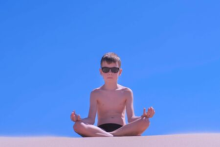Boy in swimming trunks and sunglasses is relaxing on vacations. Child boy is meditating sitting in lotus pose on sandy beach on blue sky background. Yoga breath practice. Travel tourism in summer.