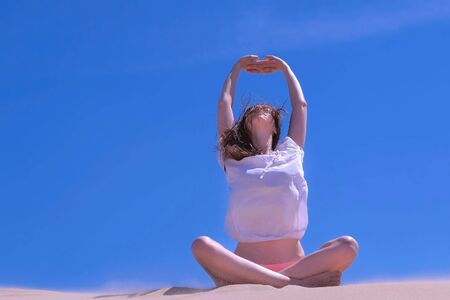 Woman practicing yoga sitting in lotus pose on sandy beach in windy day. She is stretching her arms raising hands up on blue sky background. Wears in swimsuit and blouse. Travel tourism on vacation. Zdjęcie Seryjne