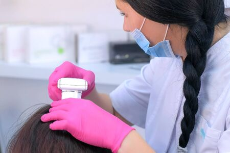 Trichologist examines woman patients hairs using computer trichoscopy in clinic. Runs a trichoscope over head skin and looks at hairs on monitor screen. Diagnostic of hair follicles to cure.