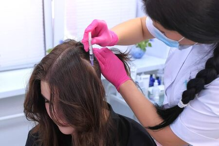 Vitamins for hairs. Doctor trichologist making injections mesotherapy in young woman skin head for hair growth in cosmetology clinic. Cosmetologist making treatment procedure to patient. Zdjęcie Seryjne