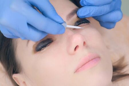 Beautician applying solution on lashes uses brush after lamination lift procedure in beauty salon, face closeup. Cosmetologist making lash lifting in cosmetology clinic.