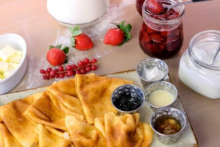 Traditional russian pancakes, blini. Served with jams, sour cream, milk and strawberry on the plate. Side view Zdjęcie Seryjne