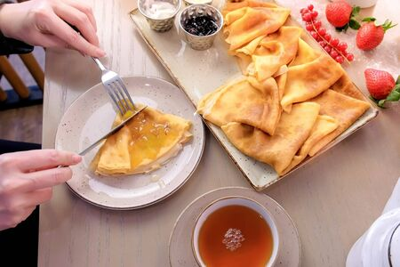 Woman is eating russian traditional pancakes, blini served with jams, sour cream, and strawberry on the plate. And drinks tea. Close-up side view