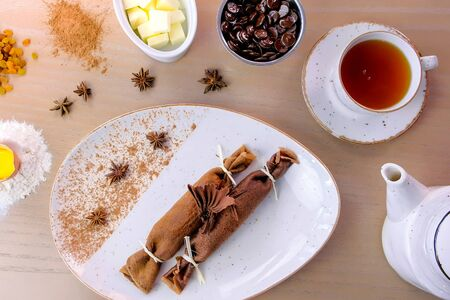 Chocolate russian pancakes, blini with curd filling on the plate. Served with a cup of tea and chocolate Zdjęcie Seryjne