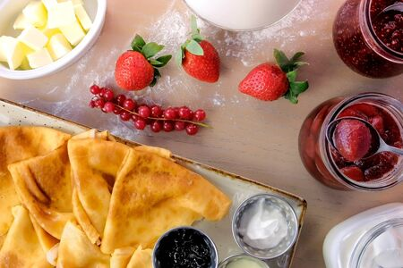 Traditional russian pancakes, blini. Served with jams, sour cream, milk and strawberry on the plate. Top view