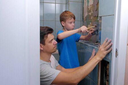 Dad and son make repairs together at home, remove tiles from walls in toilet using tool spatula. Boy knocks with hammer on putty knife. Family engaged in construction and renovation work.