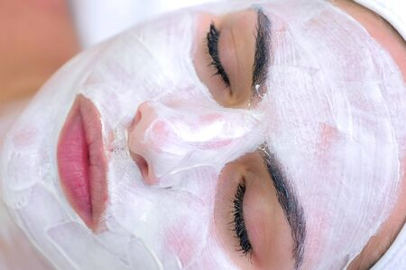 Portrait of woman laying in spa salon with white mask on face, top view. Beauty facial skincare procedure to patient in cosmetology clinic, face closeup. Beauty industry concept.