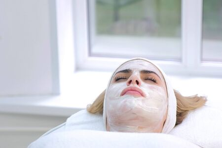 Portrait of woman laying in spa salon with white mask on face, bottom view. Beauty facial skincare procedure to patient in cosmetology clinic, face closeup. Beauty industry concept. Stok Fotoğraf