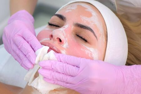 Cosmetologist in gloves wiping mask from young womans face, closeup portrait. Beautician making massaging beauty facial skincare procedure to patient in clinic. Beauty industry concept.