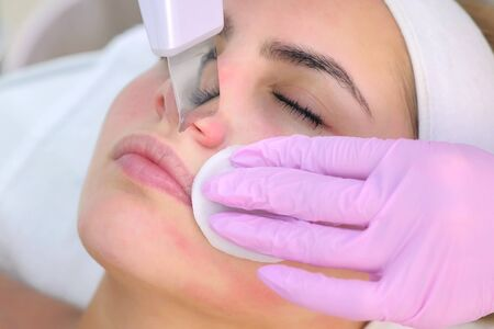 Cosmetologist making ultrasonic face cleaning procedure on nose for young woman in clinic. Closeup client portrait and beauticians hands. Procedure in cosmetology salon. Beauty industry concept. Stok Fotoğraf