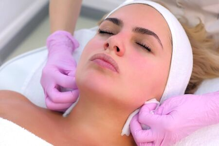 Portrait of woman client on facial cleansing procedure that washes hands of beautician. Cosmetologist making beauty procedure to patient relaxing in clinic. Beauty industry concept.